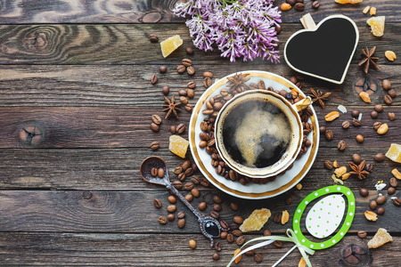 Rustic wooden background with cup of coffee and Easter decorations. Hot beverage with heart chalkboard. Top view, place for text.