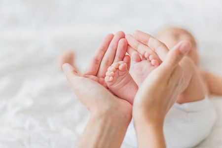 pies bonitos: La madre sostiene los pies descalzos del bebé recién nacido. Diminutos pies en la mano de mujer. Acogedora mañana en casa. Foto de archivo