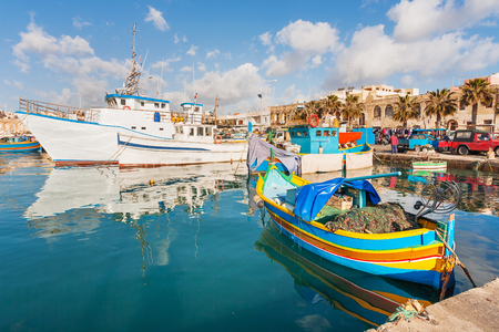 Mediterranean traditional colorful boats luzzu. Fisherman village in the south east of Malta. Early winter morning in Marsaxlokk, Malta. Banco de Imagens