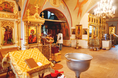 Interior of Orthodox church. Symbolic Orthodox gold cross with the crucifixion of Jesus, golden candleholders and other details.