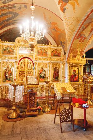 pila bautismal: Golden religious utensils - Bible, cross, prayer book, missal, baptismal font. Interoior of Orthodox Christian Church. Russia.
