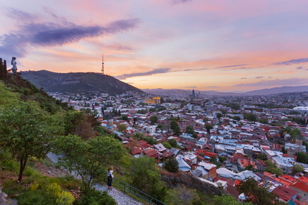 human settlement: Tourist shoots sunset panorama view of Tbilisi, capital of Georgia country, from Narikala fortress.