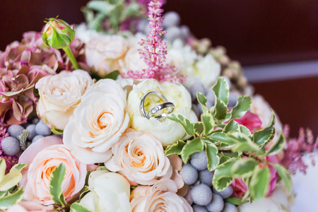 Golden wedding rings with diamonds lie inside rose flower in the bridal bouquet. Symbol of love and marriage.