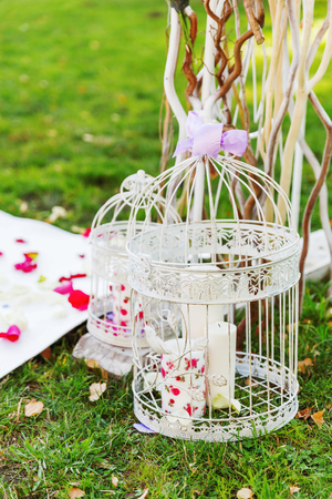 Details of beautiful floral arch for wedding ceremony. Made of bent rods with hydrangea and roses. Decorative cage with candles on ground. Wedding set up outdoors in park.