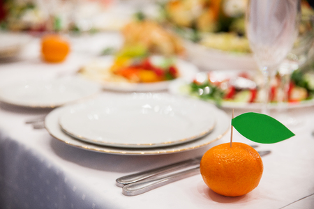 Table set for wedding banquet in orange style. Cards with names of guests stuck in the tangerines.