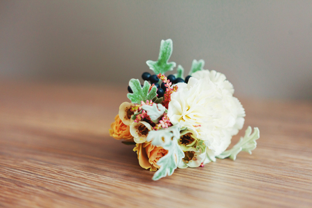 Boutonniere with peony flower on wooden background. The traditional accessory of the groom at the wedding. Stock Photo