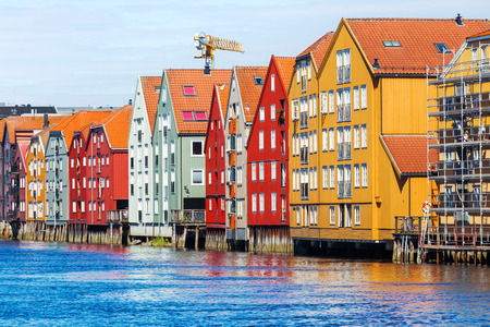 Famous wooden colored houses in Trondheim city, Norway. Colorful houses on stilts in sunny day.