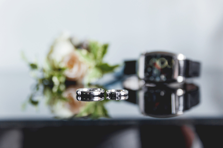 diamond ring: Pair of golden wedding rings with diamond on smooth mirror surface. Boutonniere with a rose flower and a wristwatch on background. The traditional accessories of the groom at the wedding. Stock Photo