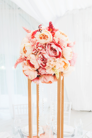 Table set for wedding banquet with floral composition of roses and peony. Flower decoration in tall vase.