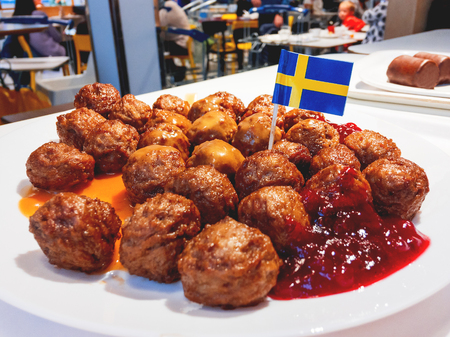 Fresh tasty meatballs with cranberry sauce on white plate with Swedish flag. Stock Photo