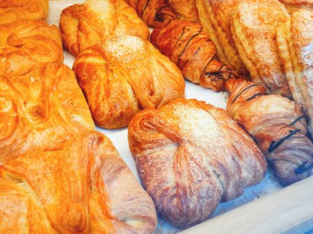 Fresh croissants lie in the shop window. Baked rolls in storefront. Tasty and fresh pastry.
