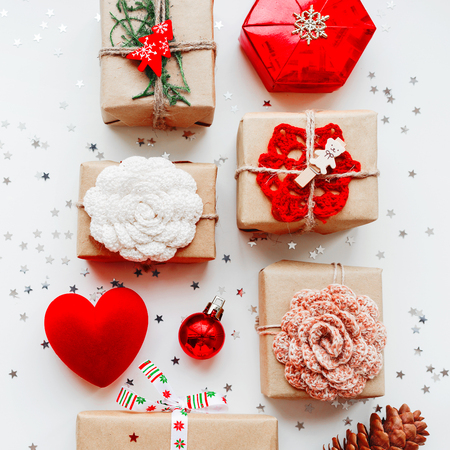 Christmas and New Year background with presents and decorations - red heart, craft paper, handmade crocheted flowers and symbols of holiday. Place for text.