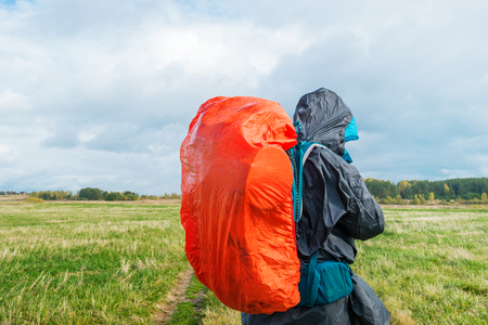 Backpacker on green field. Man hiking with bright red backpack. Autumn rural landscape.