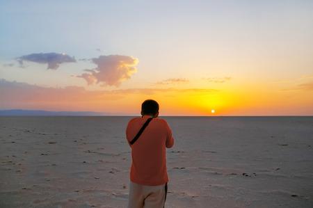 Sunrise in Sahara desert. Alone man greeted dawn at salt lake. Tourist shooting raising sun. Tunisia Reklamní fotografie