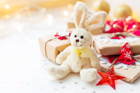 Christmas and New Year background with toy plush rabbit, presents and decorations for Christmas tree. Holiday background with stars confetti and light bulbs. Place for text.