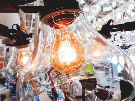 Chandelier with transparent glass plafonds and old fashioned light bulbs. Vintage light bulbs with glower filament. Incandescent, retro design.