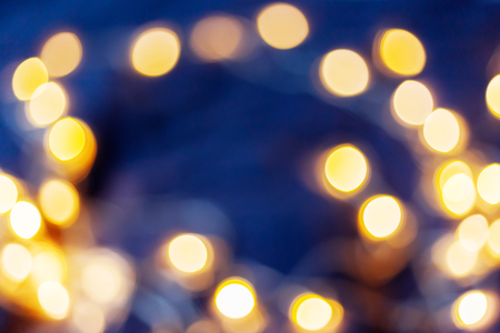 Defocused night street lights, blurred colorful bokeh background. Holiday colorful lanterns and light bulbs garlands. Stock Photo