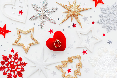 Christmas and New Year holiday background with decorations and wedding rings on gift heart box. Top view, flat lay.