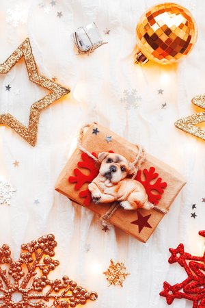 Christmas and New Year holiday background with decorations and light bulbs. Craft gift box with dog figure on it. Symbol of 2018 year. Flat lay, top view.