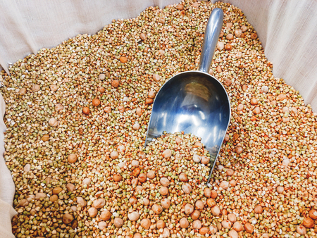 Box with green buckwheat and chickpeas. A special scoop for sprinkling grits in packages. The display in the store.