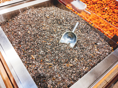 Box with sunflower seeds. A special scoop for sprinkling grits in packages. The display in the store. Stock Photo