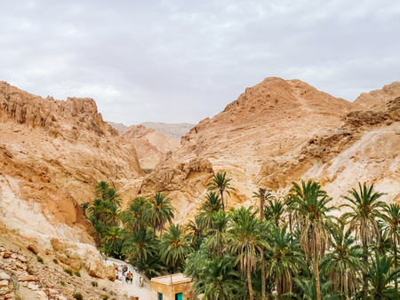 Tourists stand in line among the rocks of oasis Chebika, famous landmark in Sahara desert. Tunisia. Stock Photo