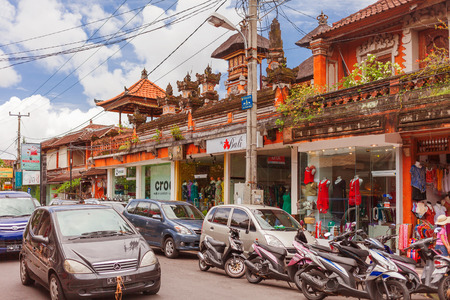 UBUD, INDONESIA - January 31, 2013. Cars moving pass souvenir shops and clothing boutiques.