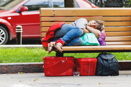 MOSCOW, RUSSIA - August 19, 2007. Homeless girl sleeping on a park bench. Moscow, Russia.