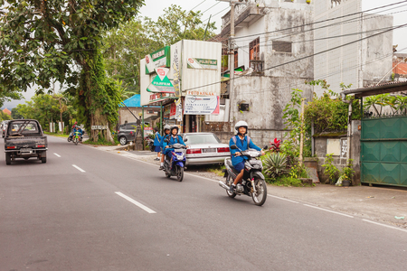 BALI, INDONESIA - January 30, 2013. Usual street life on Bali. Students and pupils drive bikes. 에디토리얼