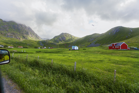 Typical scandinavian landscape with meadows, mountains and village. Lofoten islands, Norway.