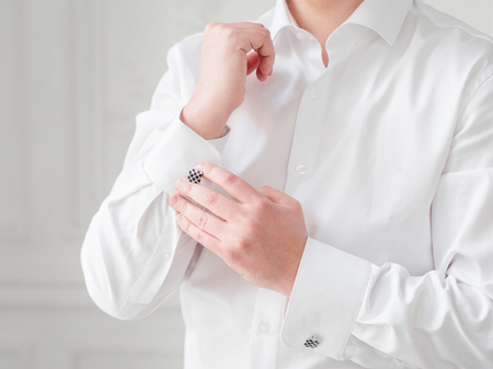 Man in white shirt adjusts his cufflinks. Groom is getting ready for wedding ceremony.