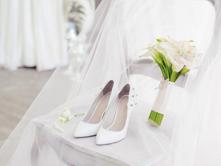 White shoes and bridal bouquet with Calla lilies. Details of wedding ceremony.  Stock Photo