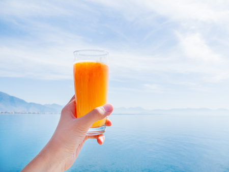 Hand with fresh tasty freshly-squeezed juice of ripe oranges in glass. Calm sea with mountains on the horizon. Kemer, Turkey.