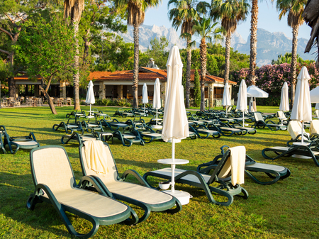 Early morning in hotel, typical for south-east part of Turkey. Sun loungers are on the lawn near sea. Kemer, Turkey. Standard-Bild
