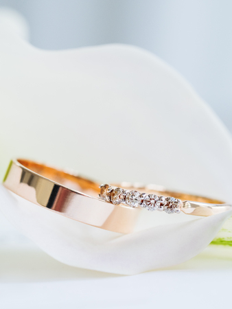 Wedding rings with diamonds in Calla lily. Details of wedding ceremony. Symbol of love and marriage.