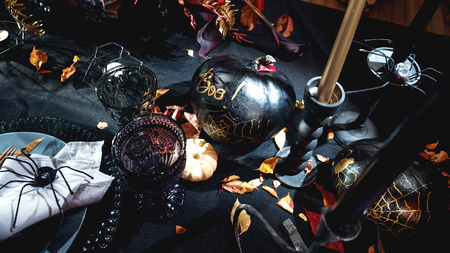 Table served in Halloween style. Bouquet with red flowers, decorative spiders, pumpkins with lettering and gothic vine glasses on black tablecloth. Holiday decorations.