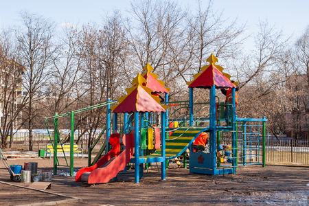 Workers of municipal services painted a playground. Children's play complex with ladders, bridges and slides. Spring in Moscow, Russia.