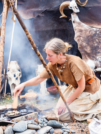 MOSCOW, RUSSIA - August 19, 2018. Woman dressed in animal skins as in ancient times. Annual festival Times and Epochs. Historical reconstruction of the Paleolithic, Mesolithic, Neolithic periods.