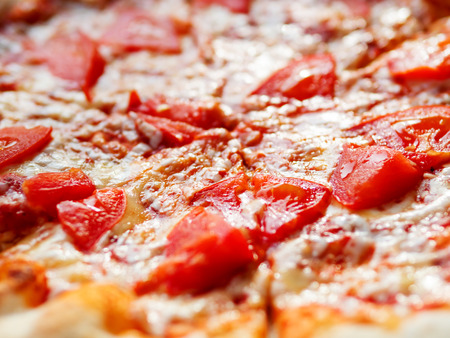 Pizza Margarita with baked ingredients - cheese with ham and tomatoes. Traditional italian cuisine. 免版税图像