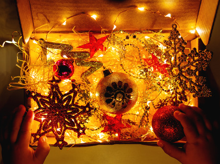 Cardboard box with Christmas and New Year decorations and light bulbs. Little baby touching red sparkling ball.