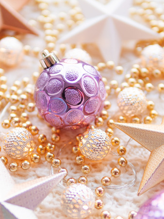 Christmas and New Year star decorations on white knitted background. Metal light bulbs with delicate pattern, golden beads and violet balls. Stock fotó