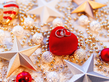 Christmas and New Year star decorations on white knitted background. Red heart gift box with wedding diamond rings, metal light bulbs with delicate pattern, golden beads. 写真素材