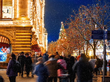 MOSCOW, RUSSIA - December 03, 2017. Streets of Moscow decorated for New Year and Christmas celebration. Crowd of people near GUM (Main Department Store) building with light bulbs. Editorial