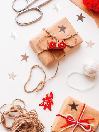 Christmas and New Year DIY presents in craft paper. Holiday gifts tied with white and red threads with toy train and Christmas tree symbol as decoration.