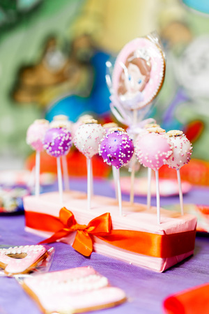 Candy bar on child birthday party. Decorated table with colorful cake pops for the guests. Imagens