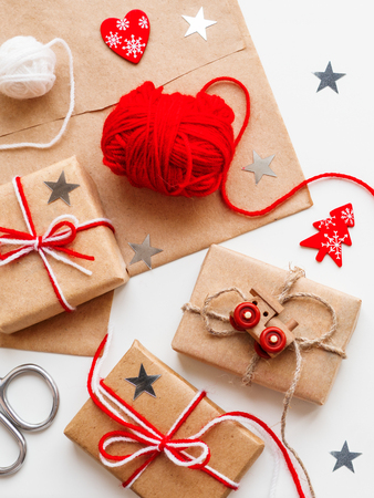 Christmas and New Year DIY presents in craft paper. Holiday gifts tied with white and red threads with toy train and red heart symbol as decoration.