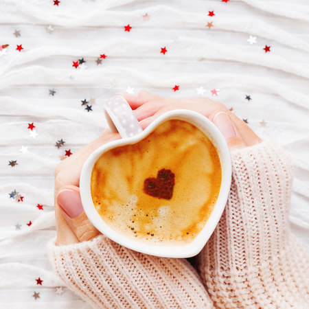 Woman holds a cup of hot coffee with cinnamon heart. Winter and Valentines Day fabric background with sparkling silver and red confetti.