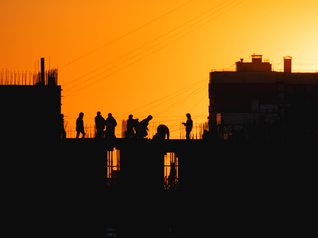 Construction of residential building. Builders go on the unfinished floor with protruding fittings. Silhouettes of workers on the background of an orange sunset. Фото со стока