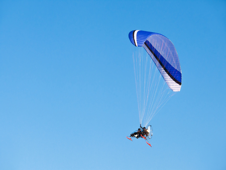 Man flying on paraglider, glider with motor. Vehicle in clear blue sky.