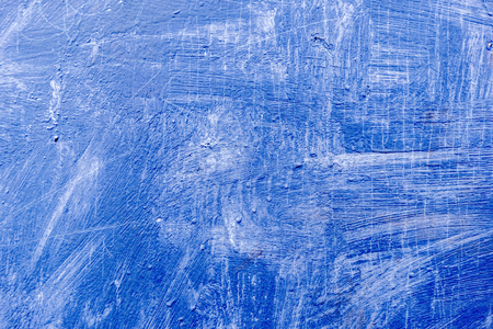 Abstract background with textured strokes of blue paint on the wooden surface.